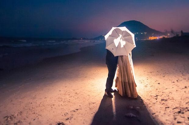 The shadow of the couple inside the white umbrella